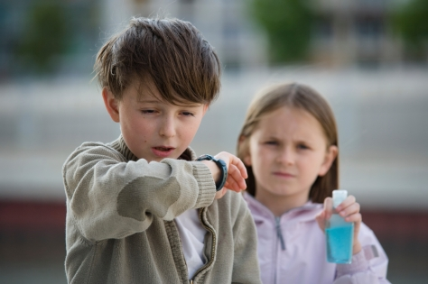 Two children stand in an urban setting, one sneezing into their elbow, the other holding a bottle of soapless hand cleanser.